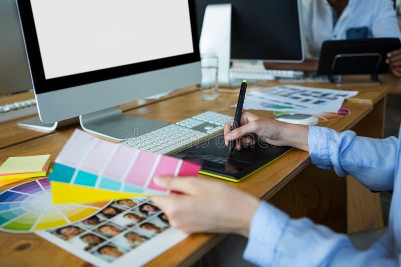 Конец-вверх женского график-дизайнера используя таблетку графиков на столе стоковая фотография rf