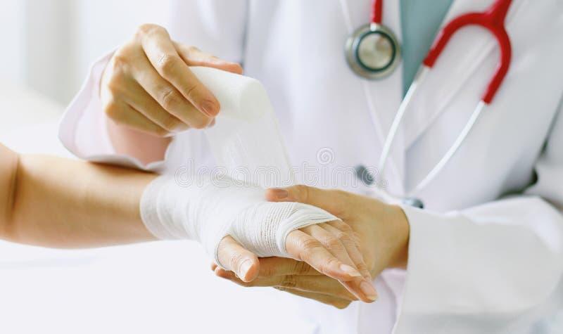Конец-вверх женского доктора с стетоскопом перевязывая руку пациента стоковое фото rf