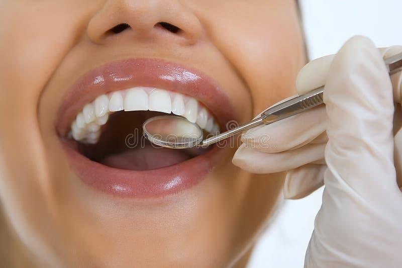 Конец-вверх женского пациента имея ее зубы быть расмотренным дантистом стоковое изображение