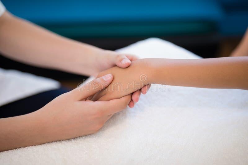 Конец-вверх женского терапевта держа руки пока рассматривающ на белом полотенце стоковые изображения