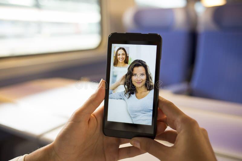 Конец-вверх женской руки держа сотовый телефон во время vid skype стоковая фотография rf
