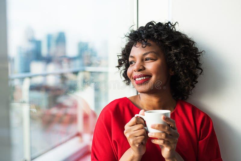 Конец-вверх женщины готовя окно держа кофейную чашку стоковое фото rf