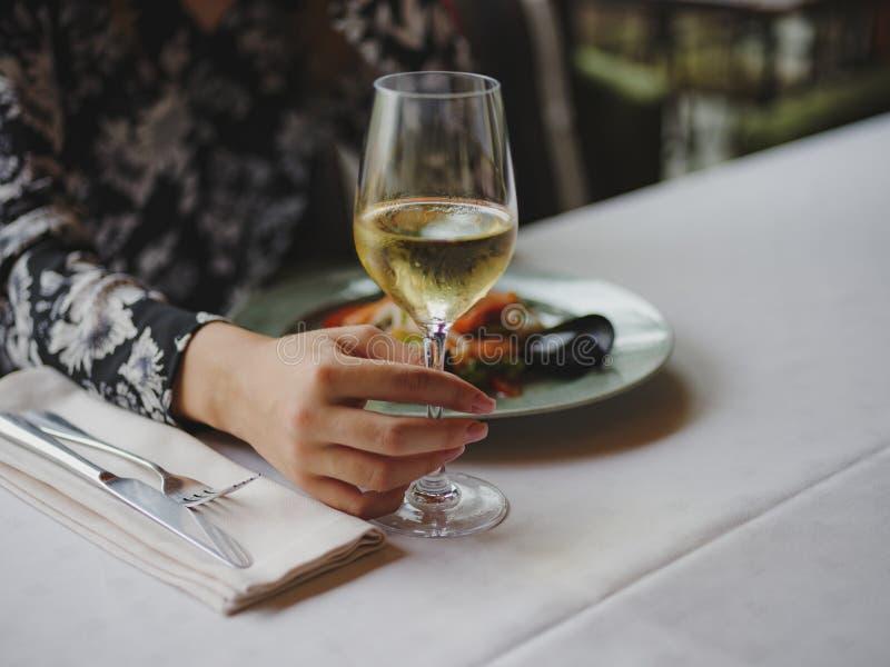 Конец-вверх женщины на ресторане Дама держа вино на запачканной предпосылке Роскошная концепция обеда скопируйте космос стоковая фотография rf