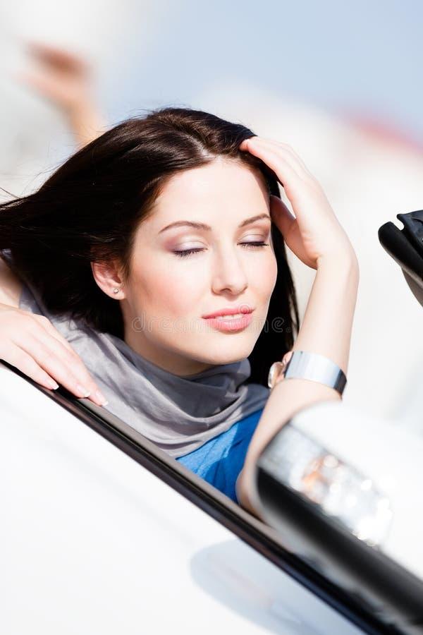 Конец вверх женщины с ее глазами закрыл в автомобиле стоковое фото