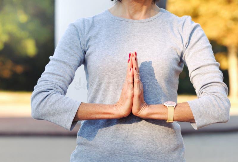 Конец вверх женщины тела делая жест namaste outdoors стоковая фотография