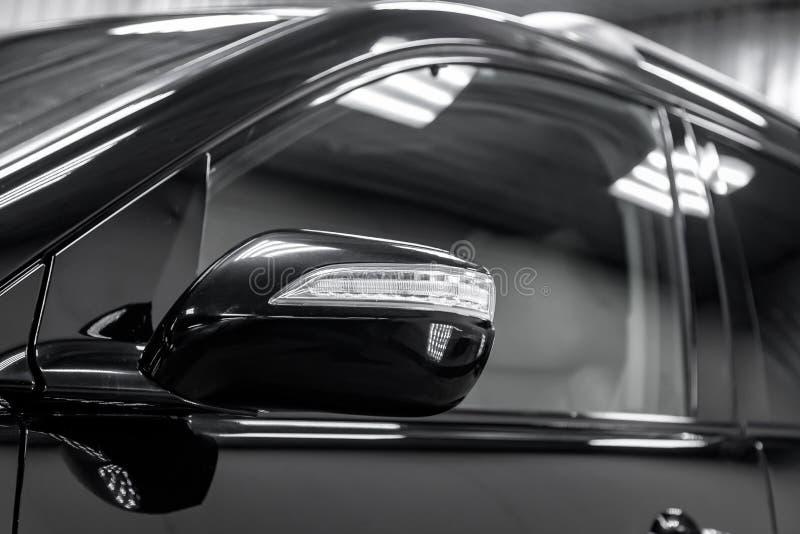 Конец-вверх зеркала седана черноты тела автомобиля на стоянке улицы стоковое изображение