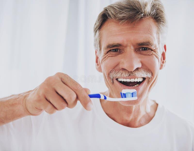 конец вверх Зубы старшего человека чистя щеткой в ванной комнате стоковые изображения