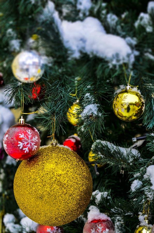 Конец-вверх игрушки рождественской елки на покрытой снег рождественской елке накануне Нового Года и рождества праздника стоковые фото