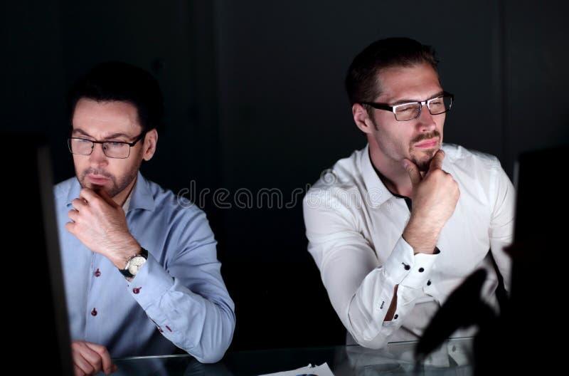 конец вверх 2 коллеги работая поздно на офисе стоковое изображение rf