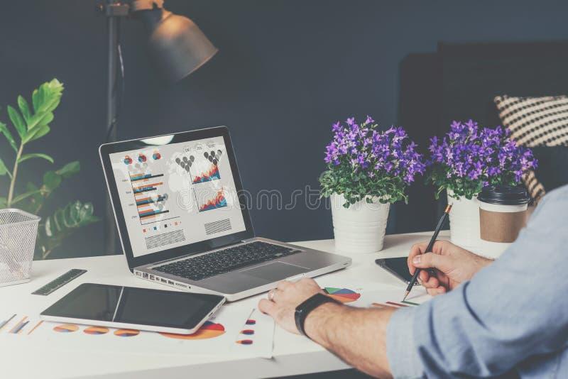 Конец-вверх компьтер-книжки с диаграммами, диаграммами и диаграммами на экране На таблице цифровая таблетка, бумажные графики, за стоковое фото