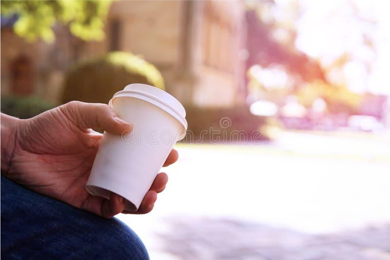 Конец вверх кофейной чашки мужского взятия удерживания руки отсутствующей на ti утра стоковая фотография rf
