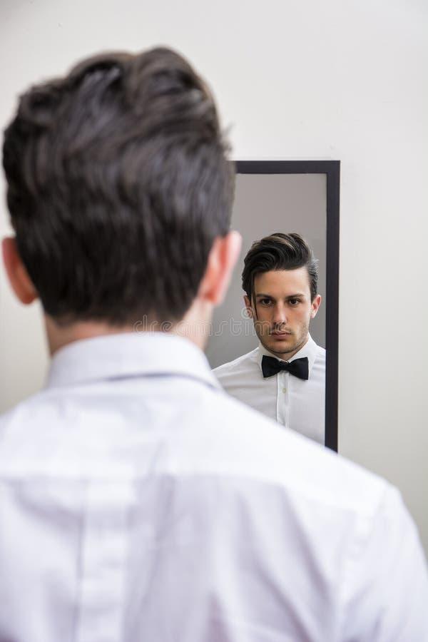 Конец-вверх красивого человека в бабочке смотря зеркало стоковые изображения rf