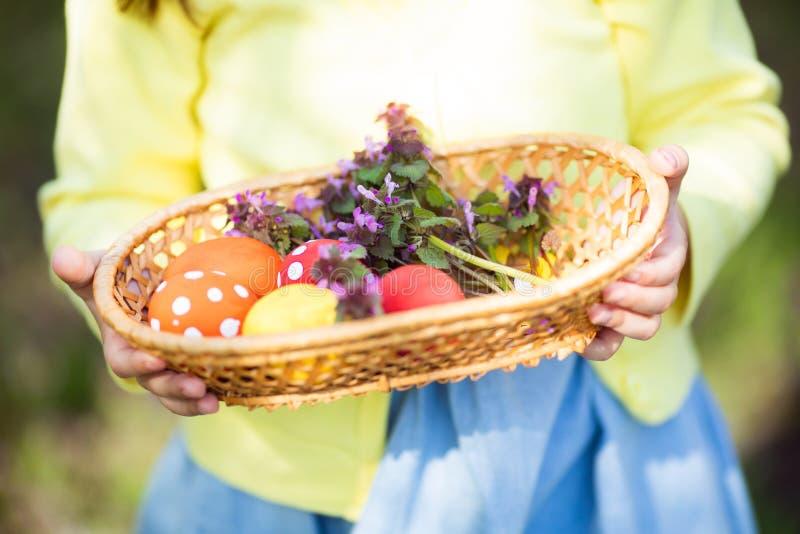 Конец-вверх красочных пасхальных яя в корзине на руках ребенка стоковое фото