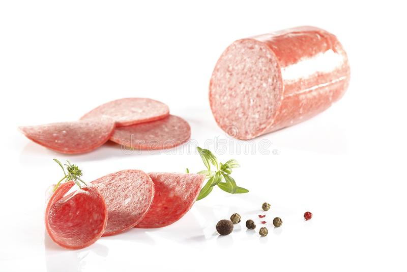 Конец-вверх кусков салями и черного и красного перца на задней части белизны стоковая фотография