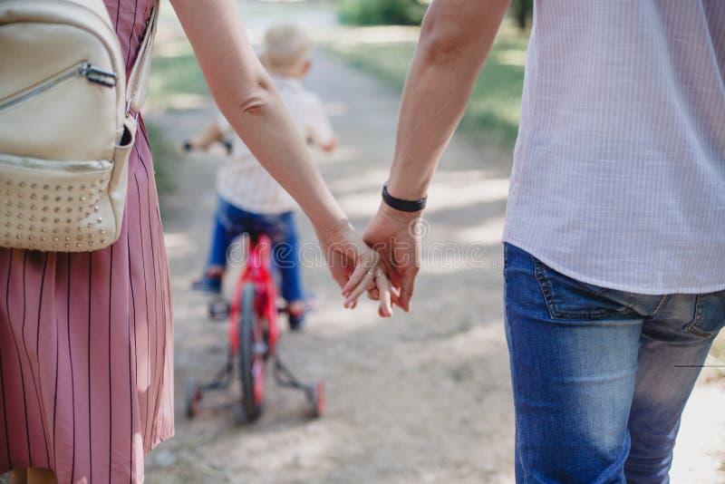 Конец-вверх любящих пар держа руки пока идущ outdoors Семья идя в парк Ребенок ехать велосипед стоковая фотография