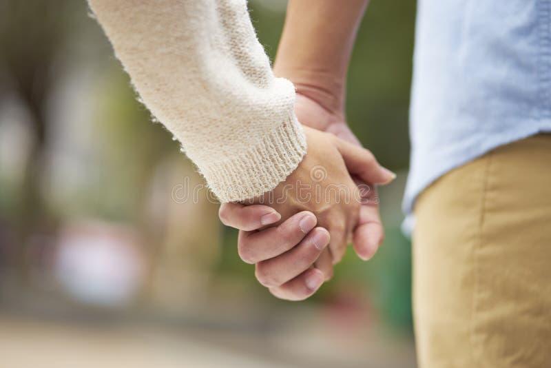 Конец-вверх 2 людей в влюбленности держа показ рук внешний романский стоковая фотография