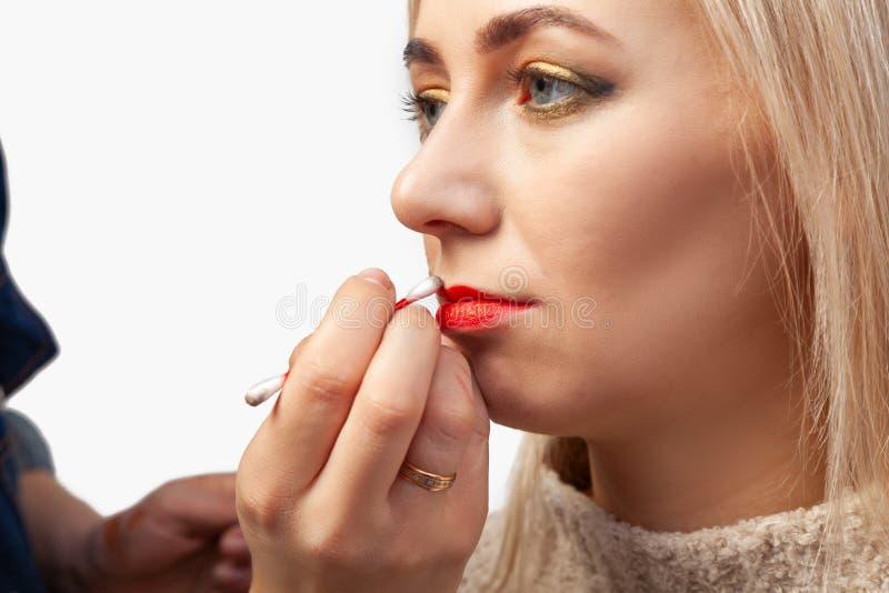 Конец-вверх макияжа губ модели с цвета свет стороной, художник макияжа держит пробирку хлопка в его руках и стоковое изображение