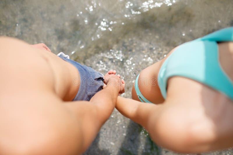 Конец-вверх мальчика и девушки держа руки на предпосылке пляжа Молодые парень и подруга Подростковая романская концепция стоковые фото