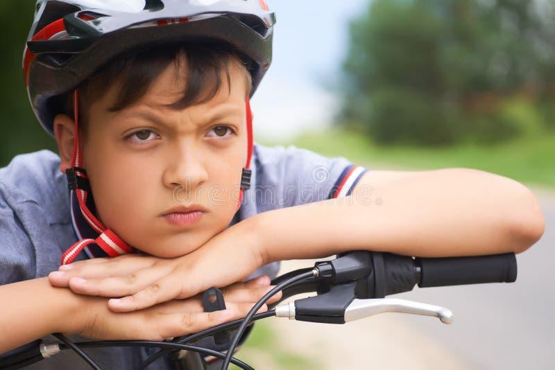 Конец-вверх мальчика подростка в защитном шлеме сидя на его велосипеде и держит его голову на его руках отдыхая на стоковое фото rf