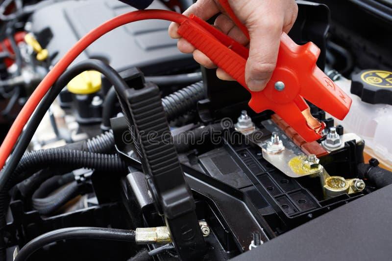 Конец-Вверх механика прикрепляя соединительные кабели к автомобильному аккумулятору стоковая фотография