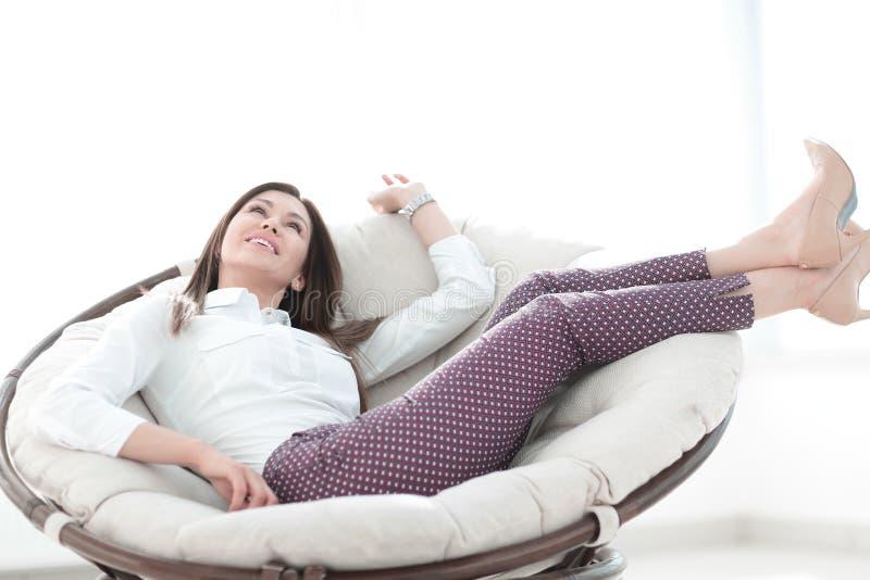 конец вверх мечтать женщина сидя в удобном стуле стоковое изображение