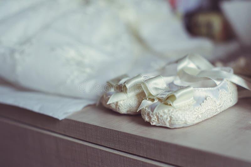 Конец-вверх милых ботинок младенца на светлой деревянной предпосылке Стильные ботинки ` s детей Белое ` s детей обувает место для стоковые изображения rf