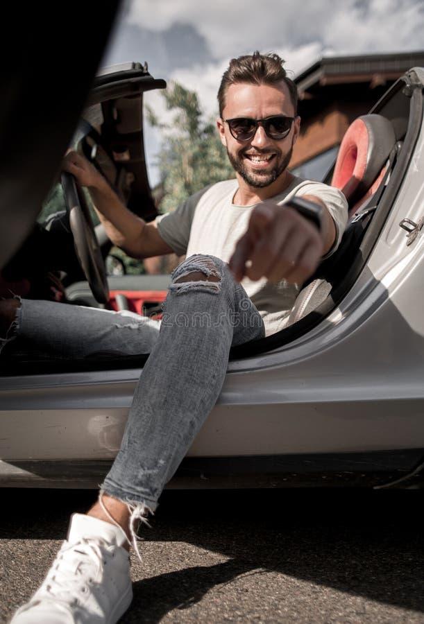 конец вверх модный молодой человек сидя в автомобиле с откидным верхом и poin стоковое фото rf