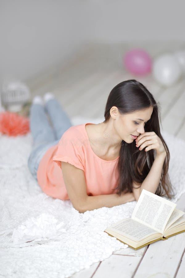 конец вверх молодая женщина читая книгу лежа на поле в живущей комнате стоковые изображения