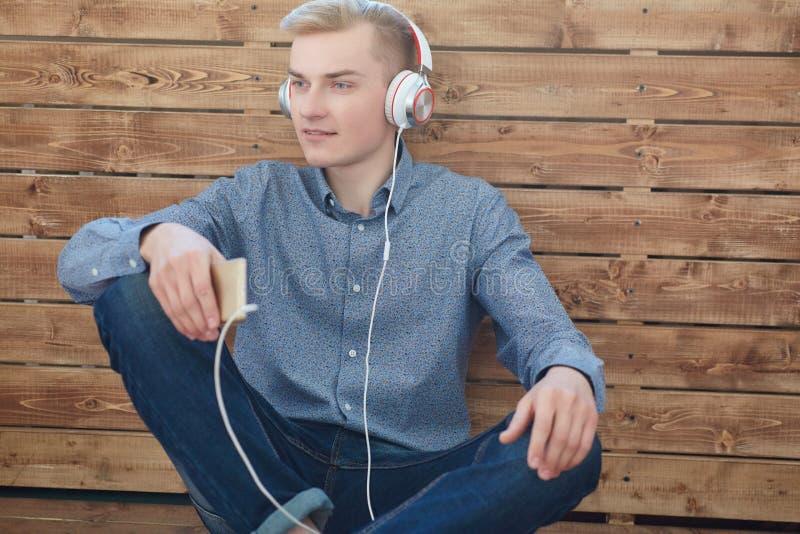 Конец-вверх молодого скандинавского человека держа мобильный телефон и слушая музыку с улыбкой пока сидящ на деревянном поле стоковые фото