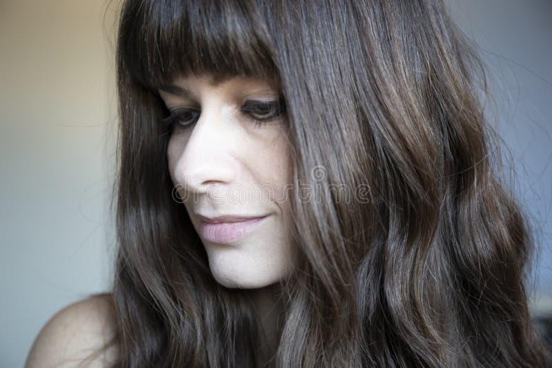 Конец-вверх молодой женщины 3/4 портретов Кавказец с коричневыми длинными волосами и челками стоковая фотография rf