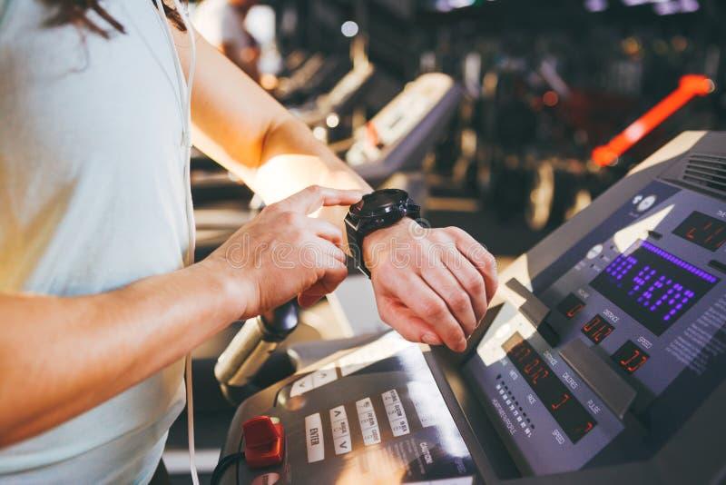 Конец-вверх молодой кавказской руки ` s женщины в спортзале использует вахту спорт, черное запястье руки ИМПа ульс на задней част стоковая фотография rf