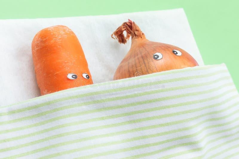 Конец-вверх моркови при лук-порей лежа совместно в кровати стоковое изображение
