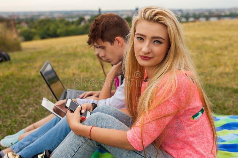 конец вверх Молодая счастливая девушка держа мобильный телефон в парке На стоковые фотографии rf