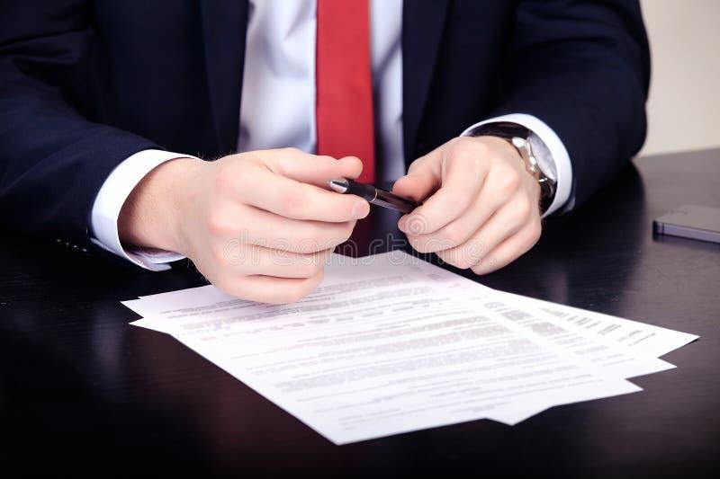 Конец-вверх мужских рук с ручкой над документом стоковое изображение