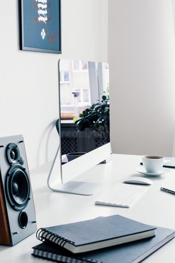 Конец-вверх на белом столе с книгами, дикторами и настольным компьютером в интерьере места для работы Реальное фото стоковое фото