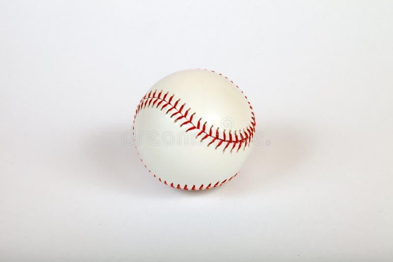 Конец-вверх на белом шарике бейсбола сшитом с красным толстым потоком сделанным из неподдельной кожи для американской игры команд стоковые изображения