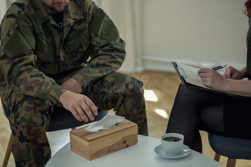 Конец-вверх на плача солдате достигая для ткани во время консультации с терапевтом стоковые изображения