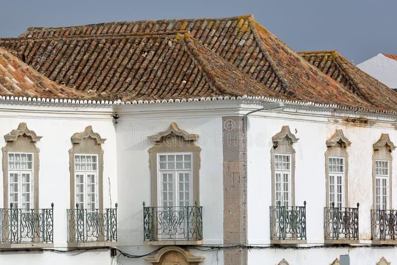 Конец-вверх на старом здании с крышами конструированными с восточным стилем и чугунными прокладывая рельсы балконами, Tavira, Алг стоковая фотография