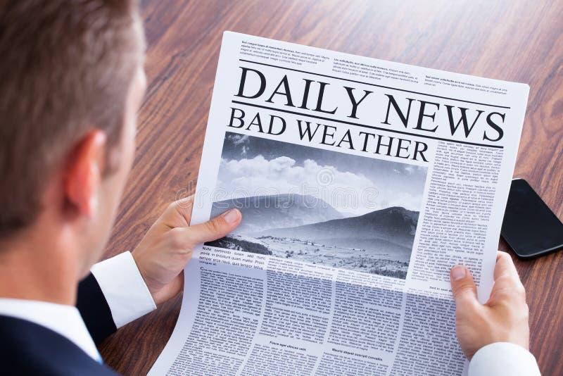 Конец-вверх новостей погоды чтения бизнесмена стоковые фотографии rf