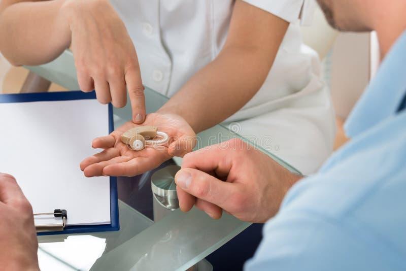 Конец-вверх доктора показывая аппарат для тугоухих к пациенту стоковые фотографии rf