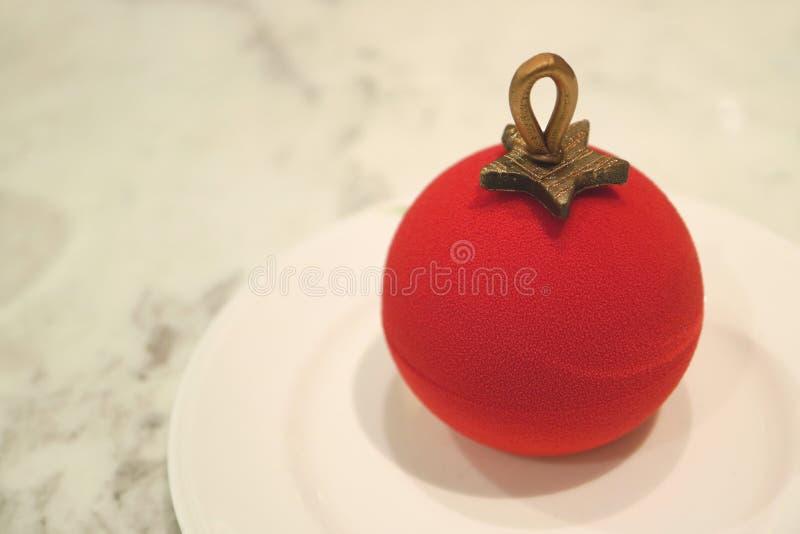 Конец вверх орнамента шарика рождества сформировал красный торт бархата при внутренность мусса ягоды, который служат на белой мра стоковая фотография