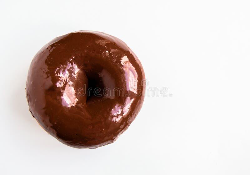 Конец-вверх очень вкусного донута с лоснистой поливой зеркала шоколада изолированной на белой предпосылке r стоковые фото