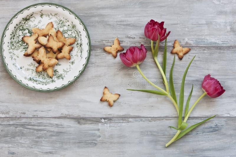 Конец-вверх печений милых бабочки на плите и beautful красных тюльпанах на винтажной серой предпосылке взгляд сверху, конец вверх стоковая фотография