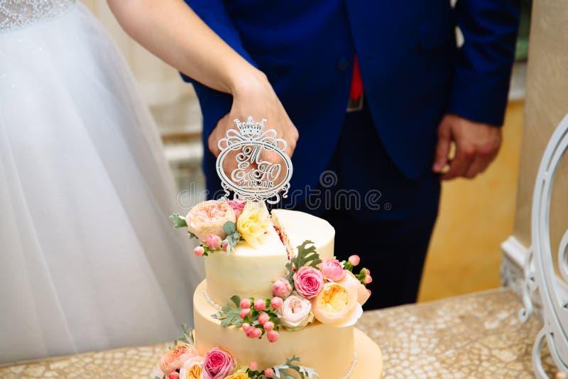 Конец-вверх подрезанной рамки жениха и невеста совместно нежно отрезает их плюш wedding золотой торт венчание стоковые фотографии rf