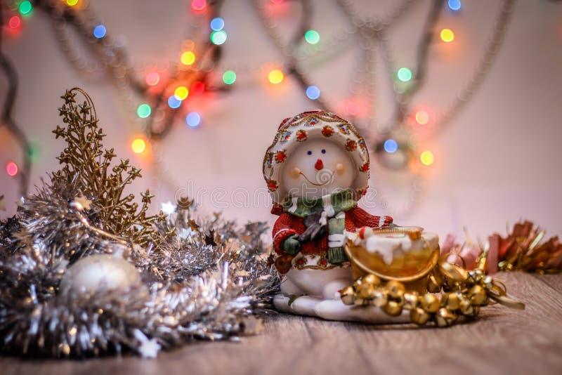 Конец-вверх подсвечника снеговика с праздничной гирляндой На фоне покрашенных светов стоковые изображения rf