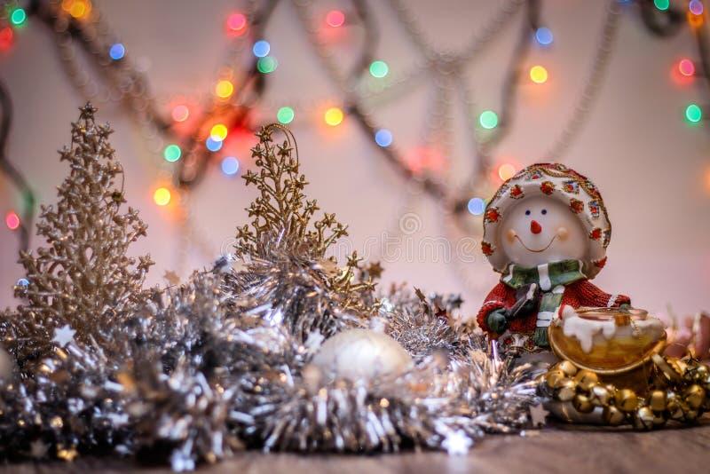 Конец-вверх подсвечника снеговика с праздничной гирляндой На фоне покрашенных светов стоковое фото