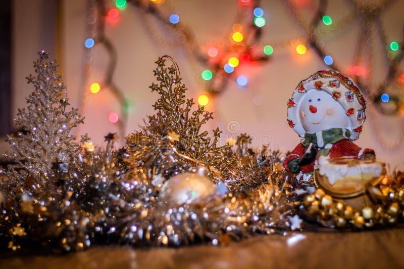 Конец-вверх подсвечника снеговика с праздничной гирляндой На фоне покрашенных светов стоковая фотография rf