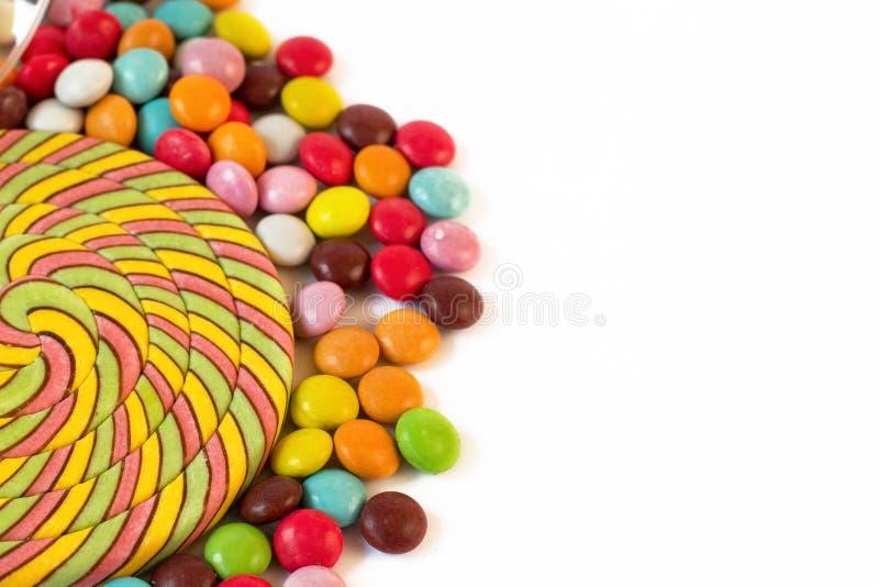 Конец-вверх покрашенного dragee конфеты леденца на палочке и десерта красочного на белой предпосылке стоковая фотография rf