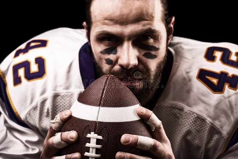 Конец-вверх портрета, американский футболист, бородатый без шлема с шариком в его руках Американец концепции стоковое фото rf