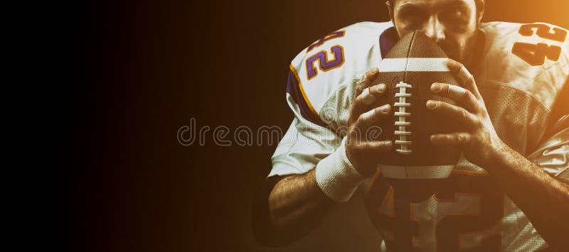 Конец-вверх портрета, американский футболист, бородатый без шлема с шариком в его руках Американец концепции стоковая фотография